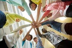 Grupo de estudiantes internacionales con las manos en el top Fotos de archivo libres de regalías