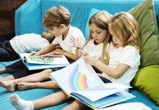 Grupo de estudiantes jovenes diversos que leen el libro Toge de la historia de los niños imagen de archivo libre de regalías