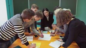 Grupo de estudiantes jovenes que hacen tarea bajo supervisión del ` s del profesor almacen de video