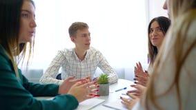 Grupo de estudiantes de la escuela secundaria que discute y que soluciona la asignación del proyecto en la tabla junto metrajes