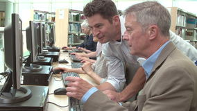 Grupo de estudiantes maduros con el profesor Working At Computers almacen de video