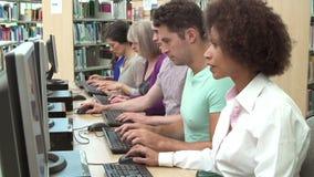 Grupo de estudiantes maduros que trabajan en los ordenadores almacen de metraje de vídeo
