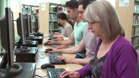 Grupo de estudiantes maduros que trabajan en los ordenadores metrajes