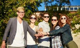 Grupo de estudiantes o de adolescentes con las manos en el top Imágenes de archivo libres de regalías