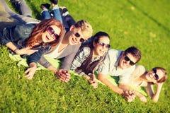 Grupo de estudiantes o de adolescentes que mienten en parque Foto de archivo libre de regalías