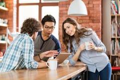 Grupo de estudiantes positivos alegres que usan el ordenador portátil en café Imagenes de archivo