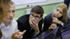 Grupo de estudiantes que discuten su proyecto junto almacen de metraje de vídeo