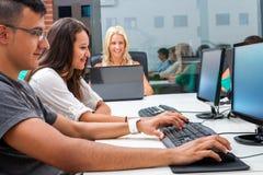 Grupo de estudiantes que entrenan en los ordenadores. Foto de archivo