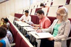 Grupo de estudiantes que escriben la prueba en la sala de conferencias Foto de archivo libre de regalías