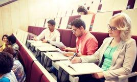 Grupo de estudiantes que escriben la prueba en la sala de conferencias fotos de archivo libres de regalías