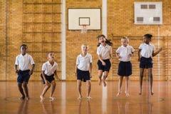 Grupo de estudiantes que saltan en gimnasio de la escuela imagenes de archivo