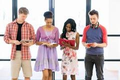 Grupo de estudiantes que se colocan con los libros Imagen de archivo libre de regalías