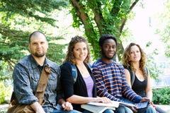 Grupo de estudiantes que se sientan en banco Foto de archivo libre de regalías
