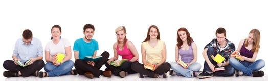 Grupo de estudiantes que se sientan en el suelo   Imágenes de archivo libres de regalías