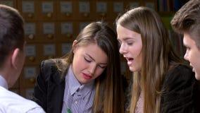 Grupo de estudiantes que se sientan en una tabla en una biblioteca metrajes