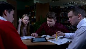 Grupo de estudiantes que se sientan en una tabla en una biblioteca almacen de video