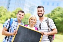 Grupo de estudiantes que sostienen una pizarra en el parque Fotos de archivo libres de regalías