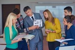 Grupo de estudiantes que trabajan con el profesor en modelo de la casa Fotografía de archivo