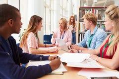Grupo de estudiantes que trabajan junto en biblioteca con el profesor Imagenes de archivo