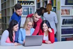 Grupo de estudiantes que trabajan junto en biblioteca con el profesor Foto de archivo libre de regalías