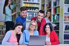 Grupo de estudiantes que trabajan junto en biblioteca con el profesor Fotografía de archivo libre de regalías