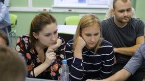 Grupo de estudiantes que trabajan junto en un nuevo proyecto educativo en la sala de clase moderna Trabajo en equipo del profesio metrajes