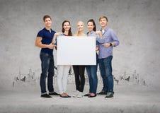 Grupo de estudiantes sonrientes con el tablero en blanco blanco Foto de archivo libre de regalías