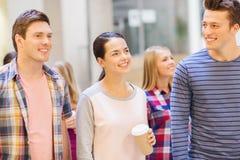 Grupo de estudiantes sonrientes con las tazas de café de papel Imágenes de archivo libres de regalías