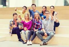 Grupo de estudiantes sonrientes con las tazas de café de papel Imagenes de archivo
