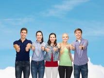 Grupo de estudiantes sonrientes que muestran los pulgares para arriba Fotografía de archivo