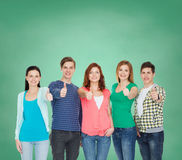 Grupo de estudiantes sonrientes que muestran los pulgares para arriba Imagenes de archivo