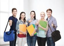 Grupo de estudiantes sonrientes que muestran los pulgares para arriba Imagen de archivo libre de regalías