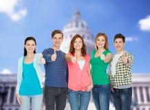 Grupo de estudiantes sonrientes que muestran los pulgares para arriba Imágenes de archivo libres de regalías