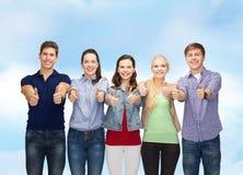 Grupo de estudiantes sonrientes que muestran los pulgares para arriba Foto de archivo