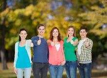 Grupo de estudiantes sonrientes que muestran los pulgares para arriba Foto de archivo libre de regalías