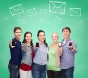 Grupo de estudiantes sonrientes que muestran smartphones Fotos de archivo libres de regalías