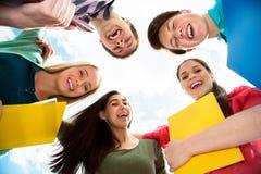 Grupo de estudiantes sonrientes que permanecen junto y que miran la cámara Foto de archivo