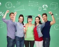 Grupo de estudiantes sonrientes sobre tablero verde Foto de archivo libre de regalías