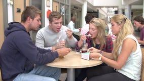 Grupo de estudiantes universitarios que comen el almuerzo junto almacen de video