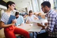 Grupo de estudiantes universitarios que estudian en la biblioteca imagen de archivo libre de regalías