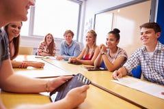 Grupo de estudiantes universitarios que se sientan en la tabla que tiene discusión fotos de archivo libres de regalías