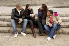 Grupo de estudiantes universitarios que se sientan en pasos de progresión Foto de archivo libre de regalías