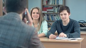 Grupo de estudiantes universitarios que se sientan en sus escritorios en auditorio y para profesor que espera, mientras que él qu Fotografía de archivo libre de regalías