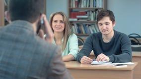 Grupo de estudiantes universitarios que se sientan en sus escritorios en auditorio y para profesor que espera, mientras que él qu Fotos de archivo libres de regalías