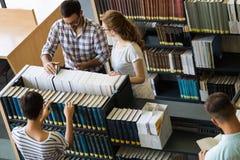 Grupo de estudiantes universitarios que trabajan junto en la escuela Fotografía de archivo libre de regalías