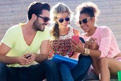 Grupo de estudiantes universitarios que usan el teléfono móvil en la calle Imagen de archivo libre de regalías