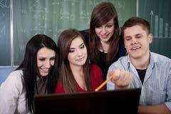 Grupo de estudiantes universitarios que usan la computadora portátil Fotografía de archivo libre de regalías