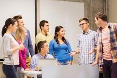Grupo de estudiantes y de profesor con el ordenador portátil Foto de archivo