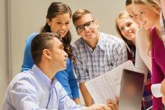 Grupo de estudiantes y de profesor con el ordenador portátil Imagen de archivo