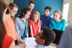 Grupo de estudiantes y de profesor con las pruebas en la escuela Fotos de archivo